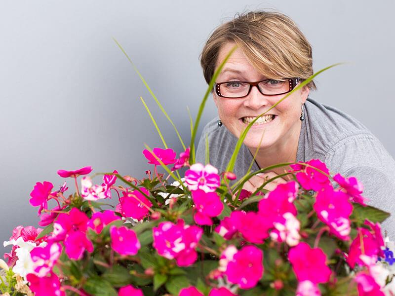 Anita Kirkbride smiles and peeks out behind pink flowers